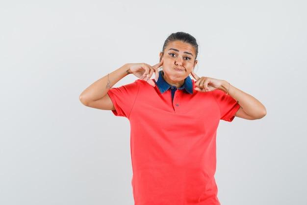 Giovane donna che sbuffa le guance, mettendo il dito indice sulle guance in maglietta rossa e sembra carina, vista frontale.