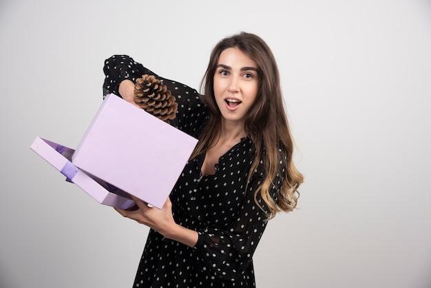 若い女性は紫色のギフトボックスから松ぼっくりを引っ張った 無料写真