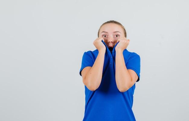 Giovane donna che tira il collare sul viso in maglietta blu e sembra spaventata