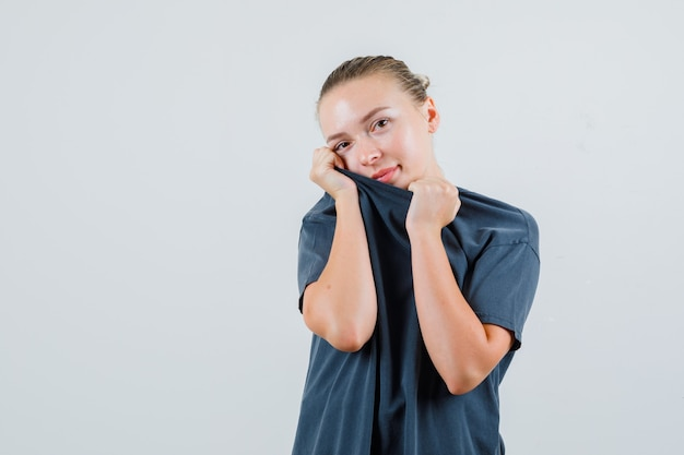 Молодая женщина в серой футболке натягивает воротник на лице и выглядит застенчивой
