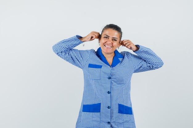 Giovane donna che tira le orecchie con le dita e sorride in camicia del pigiama a quadretti blu e sembra felice, vista frontale.