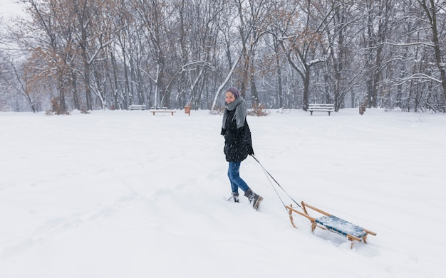 Young woman pulling empty wooden sledge on snow landscape at forest