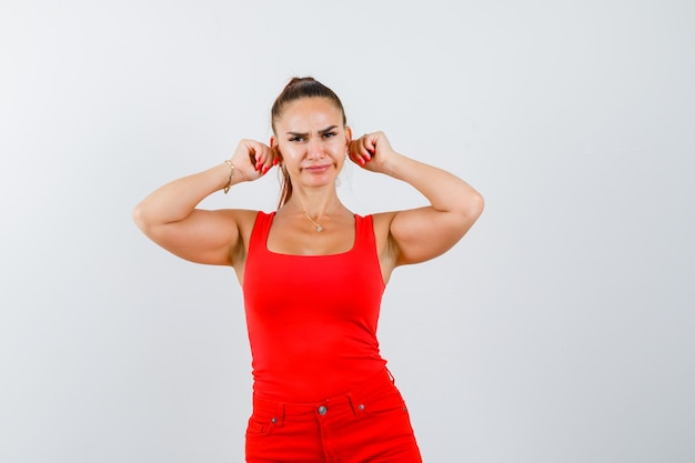 Young woman pulling her ears in red tank top, pants and looking displeased , front view.