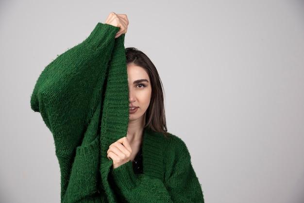 灰色のセーターを引っ張る若い女性。
