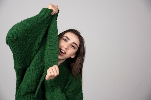 회색에 그녀의 스웨터를 당기는 젊은 여자.