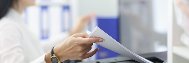 Young woman pulling paper out of printer closeup