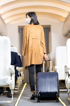 飛行機の中でスーツケースを引っ張る若い女性、商用飛行機の頭上の収納コンパートメントで機内持ち込み手荷物を見ながら荷物を持って立っている旅行者。