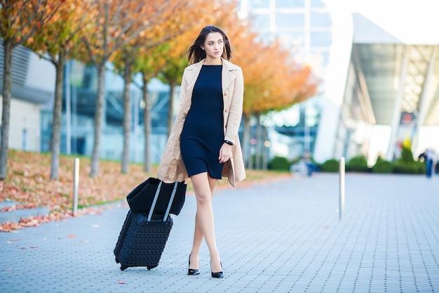 空港ターミナルの近くでスーツケースを引っ張る若い女性。