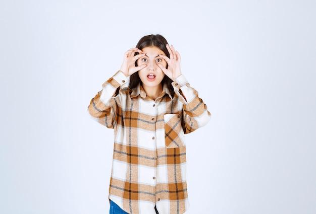 La giovane donna tira la sua zona degli occhi sul muro bianco.