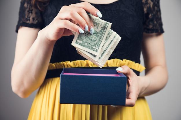 젊은 여자가 선물 상자에서 돈을 꺼냅니다