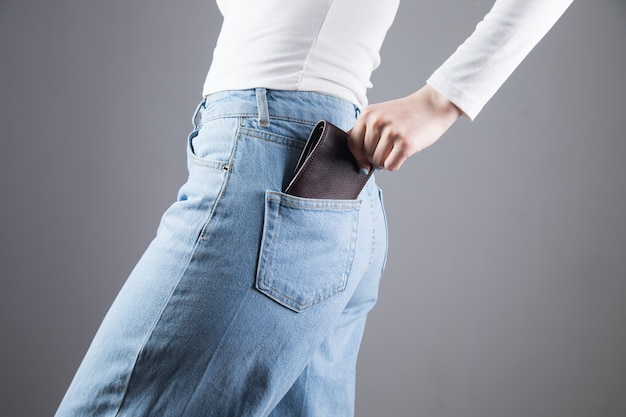 Young woman pulls out her wallet from her pocket on a gray wall