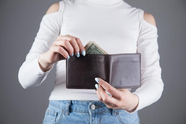Молодая женщина вытаскивает деньги из бумажника на серой стене