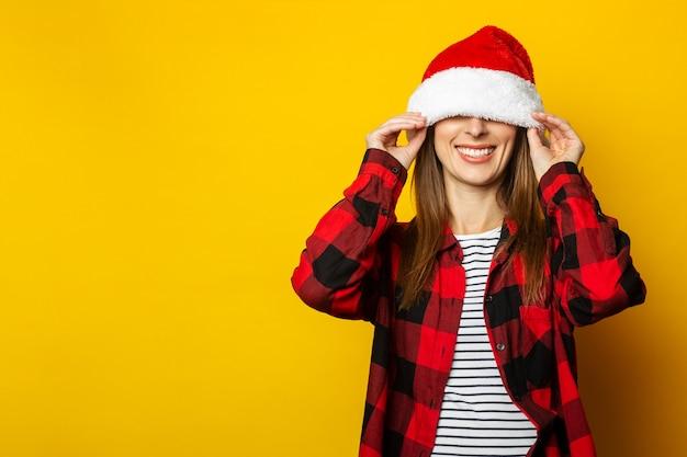 Молодая женщина тянет шляпу санта-клауса и красную клетчатую рубашку