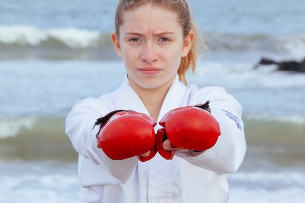 Молодая женщина, пробивая боевые перчатки
