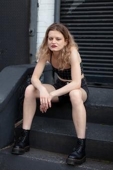 Giovane donna in abiti punk all'aperto