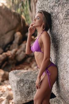 A young woman in a purple bikini poses near the rocks
