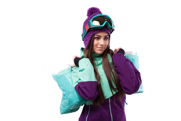 Young woman in purple ski outfit hold snow boots