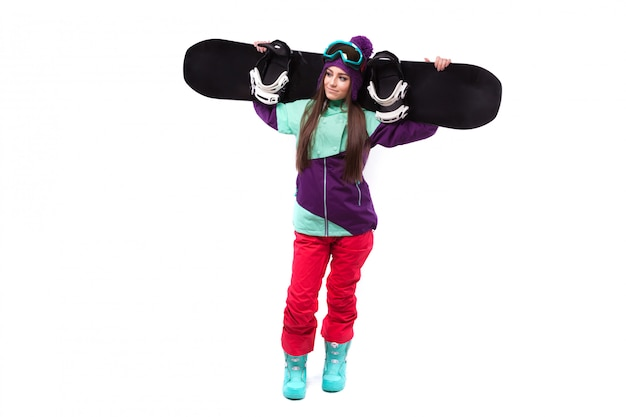 Young woman in purple ski outfit hold snowboard on sholders