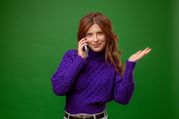 Young woman in purple sweater talking on mobile phone on green background studio