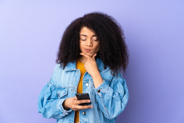 Young woman on purple thinking and sending a message