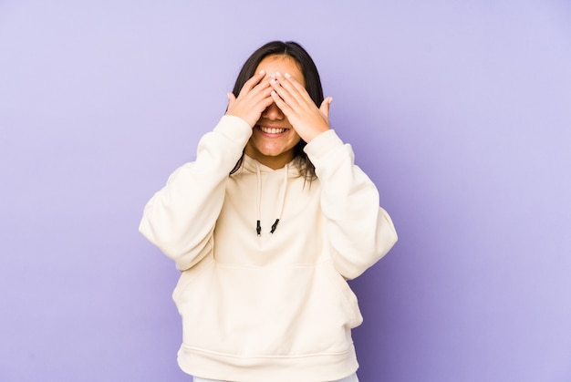 Young woman on a purple wall covers eyes with hands, smiles broadly waiting for a surprise.