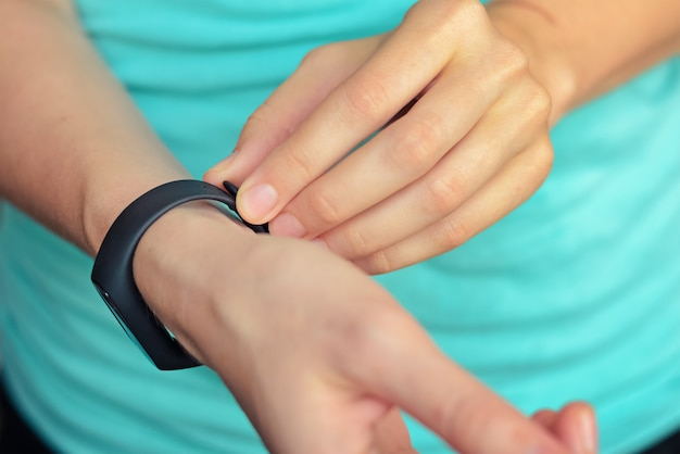 Young woman put on fitness tracker on her hand