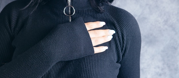 A young woman put her hand on her chest on a gray background