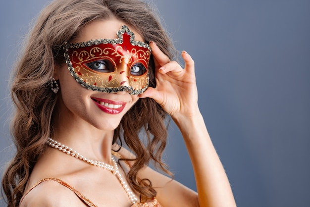 A young woman puts on a carnival mask