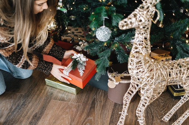 若い女性はクリスマスツリーの下にギフトボックスを置きます。