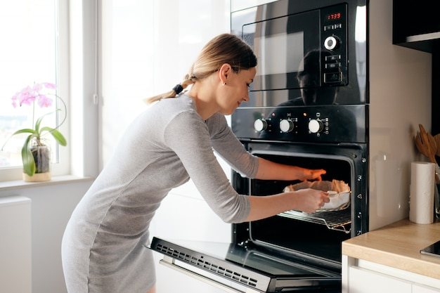 Young woman puts the homemade cake in the oven