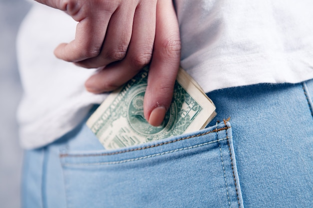 Young woman puts money in her back pocket. keep money