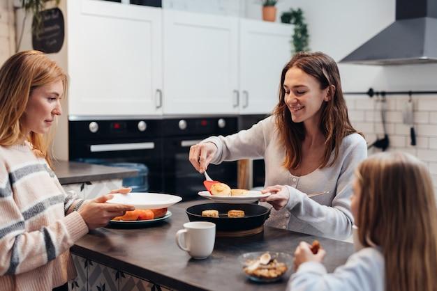 Молодая женщина кладет блины со сковороды своему другу и дочери.