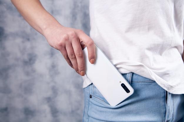 若い女性が携帯電話をポケットに入れる