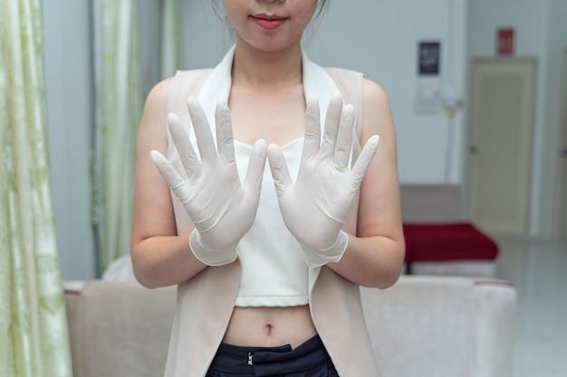젊은 여자는 흰색 라텍스 일회용 의료 장갑을 손에 넣습니다.
