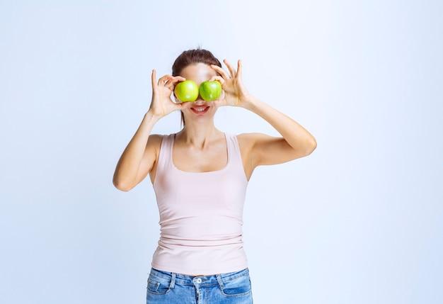Молодая женщина, прикладывая зеленое яблоко к ее глазу