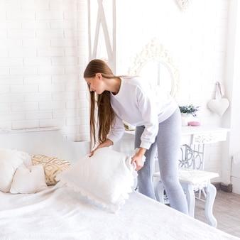 Молодая женщина кладет подушку на кровать