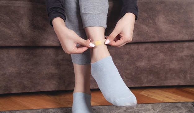 Young woman putting adhesive bandage in her leg.