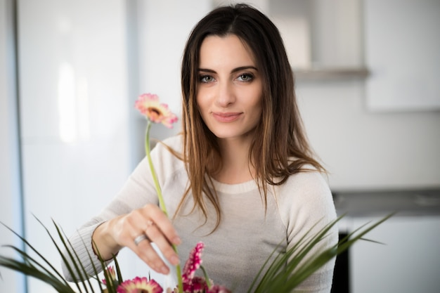 Young woman putting colorful flowers in vase