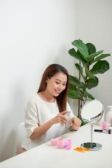 Молодая женщина наносит крем на руку, сидя за туалетным столиком