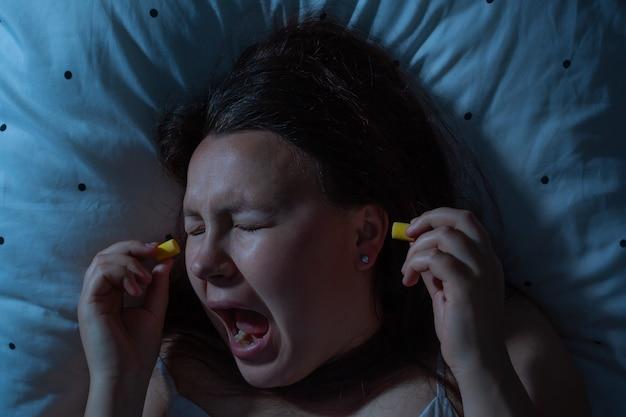 수면 전 소음 감소, 불면증을 위해 귀에 귀마개를 꽂는 젊은 여성