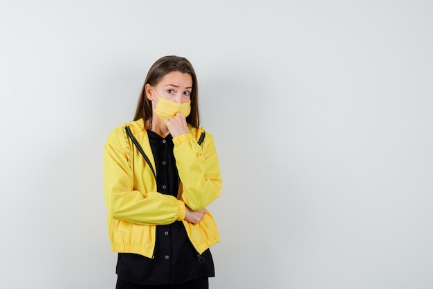 Young woman putting fist on chin and looking serious