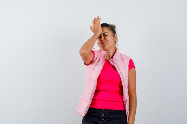 Giovane donna che mette la mano sulla fronte in maglietta e giacca rosa e sembra infastidita