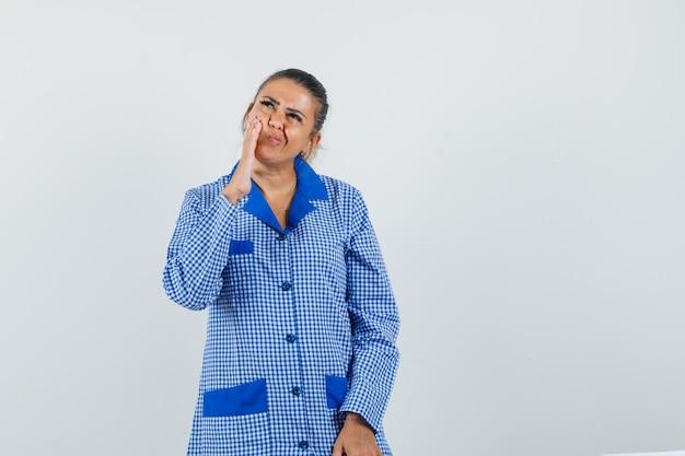 Giovane donna che mette la mano vicino alla bocca, stando in piedi nel gesto di pensiero in camicia del pigiama a quadretti blu e guardando pensieroso. vista frontale.