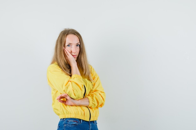 頬に手を置いて、黄色のボンバージャケットとブルージーンズでポーズを考えて立っている若い女性は、物思いにふける、正面図を探しています。