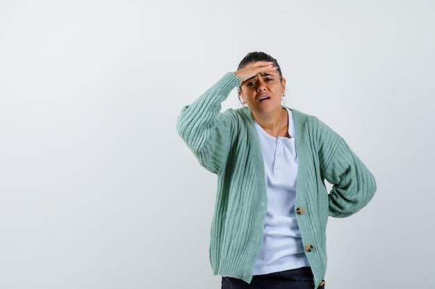 額に手を置いて、白いtシャツとミントグリーンのカーディガンで頭痛がして、疲れ果てているように見える若い女性