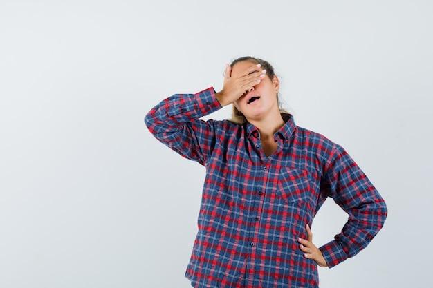 Молодая женщина кладет руку на лоб, держа руку на талии в клетчатой рубашке и выглядит усталой