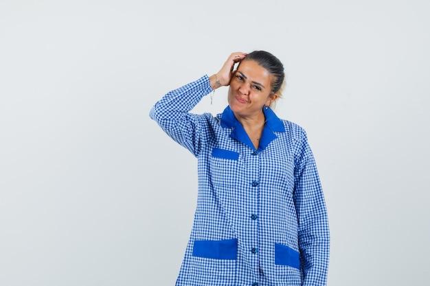 파란색 깅엄 파자마 셔츠에서 뭔가에 대해 생각하고 예쁘게 보이는 동안 머리에 손을 댔을 젊은 여자. 전면보기.