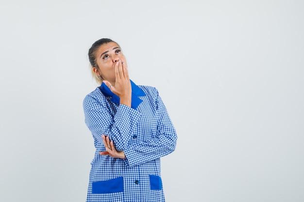 입에 손을 댔을, 파란색 깅엄 파자마 셔츠에 제스처를 생각하고 잠겨있는 찾고 젊은 여자. 전면보기.