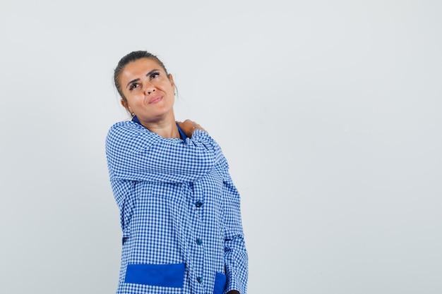 파란색 깅엄 파자마 셔츠에 어깨 통증이 있고 피곤해 보이는 젊은 여성이 어깨에 손을 댔습니다. 전면보기.