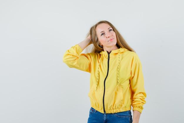 노란색 폭격기 재킷과 블루 진에 카메라에 포즈를 취하는 동안 머리 위에 손을 넣어 젊은 여자